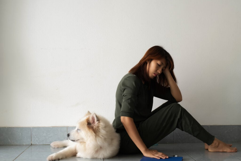 lady looking very sad about her white samoyed puppy laying behind her, does she have the puppy blues?