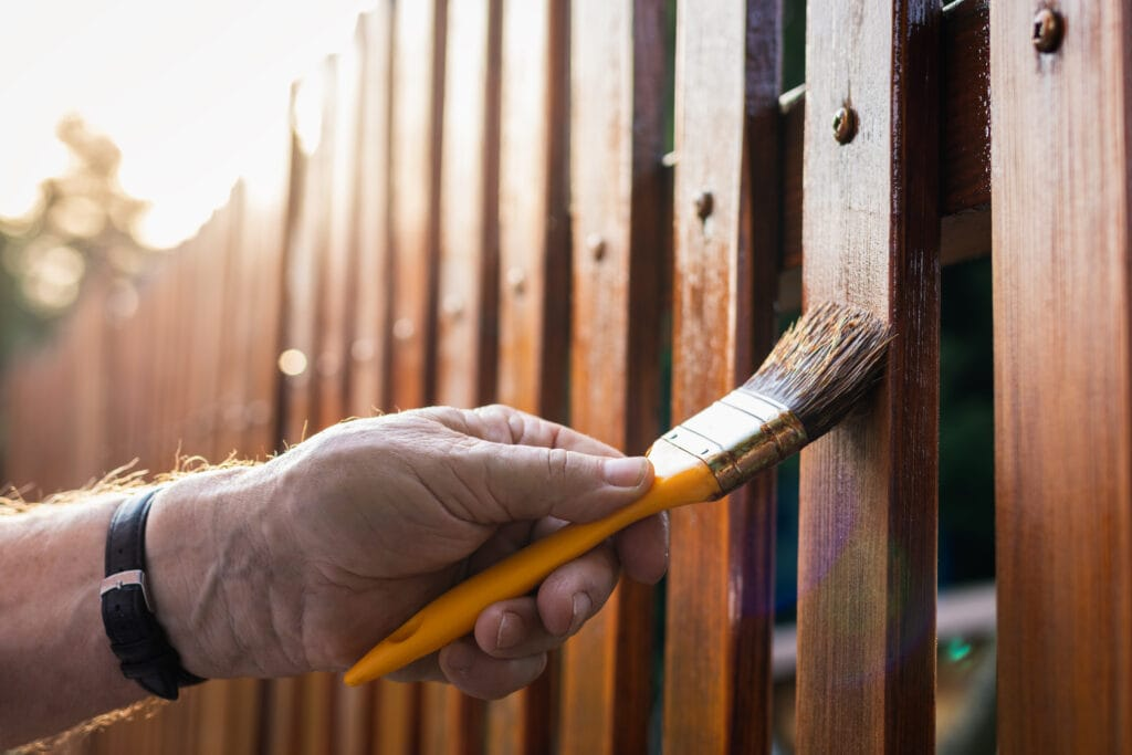 painting a physical fence takes time, but it's worth it to keep the wood strong